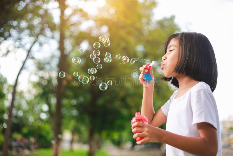 Liten asiatisk flicka som blåser bubblor i trädgården arkivfoto