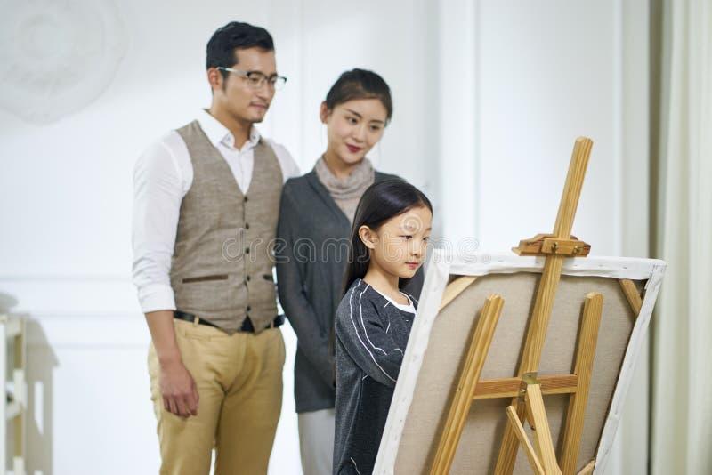 Liten asiatisk flicka som gör en målning med att hålla ögonen på för föräldrar arkivbild