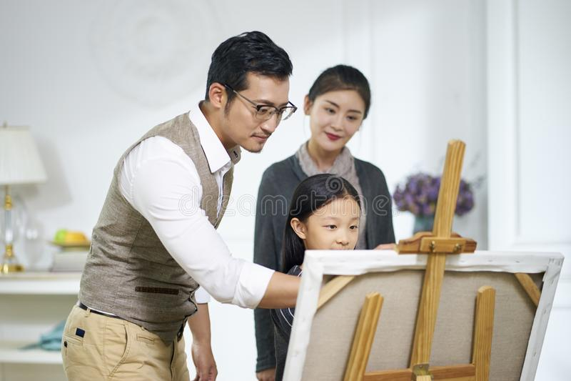 Liten asiatisk flicka som gör en målning med föräldrar som håller ögonen på och hjälper royaltyfria bilder
