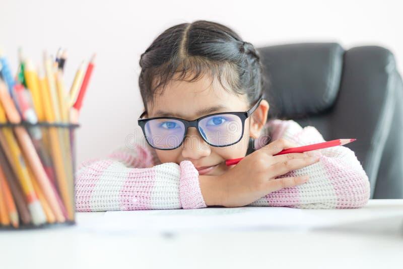 Liten asiatisk flicka som rymmer blyertspennan till att göra läxa och leende med lycka för djup för vald fokus för utbildningsbeg arkivfoton