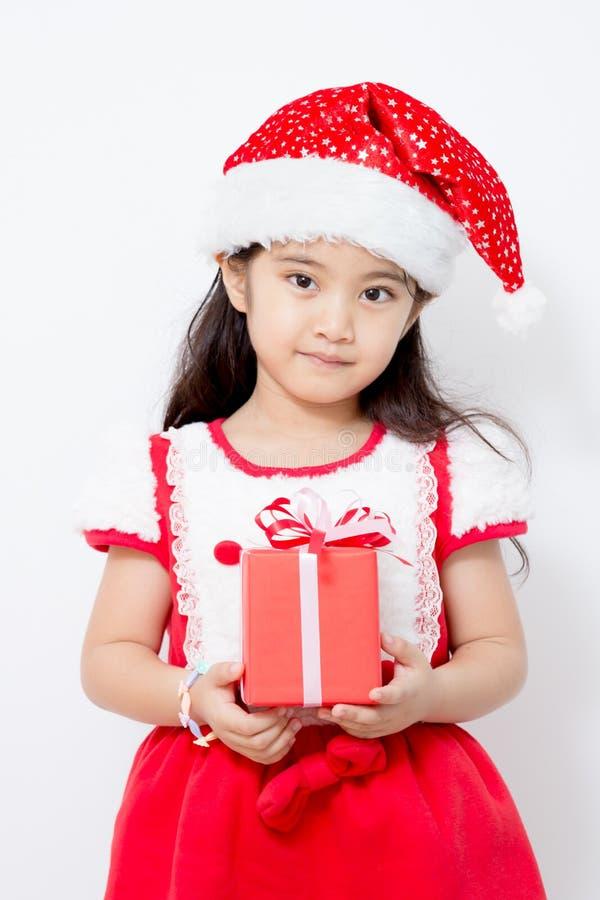 Liten asiatisk flicka som rymmer den röda gif-asken på jul arkivbild