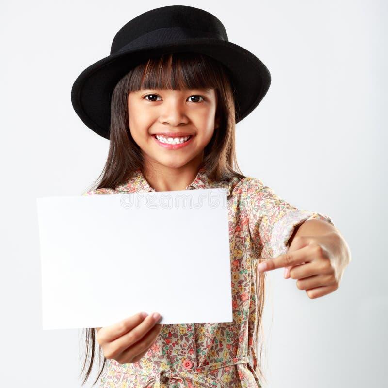 Liten asiatisk flicka som rymmer det tomma vita brädet arkivbilder