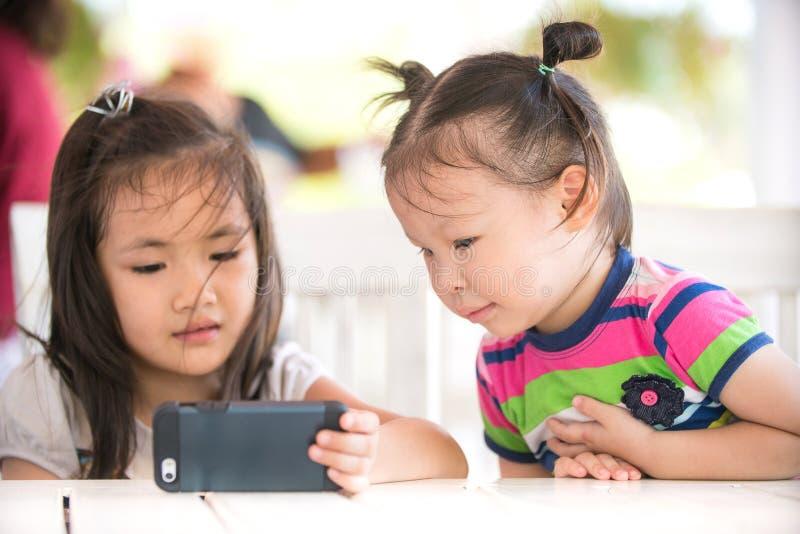 Liten asiatisk flicka som ser mobiltelefonen med hans syster royaltyfri fotografi