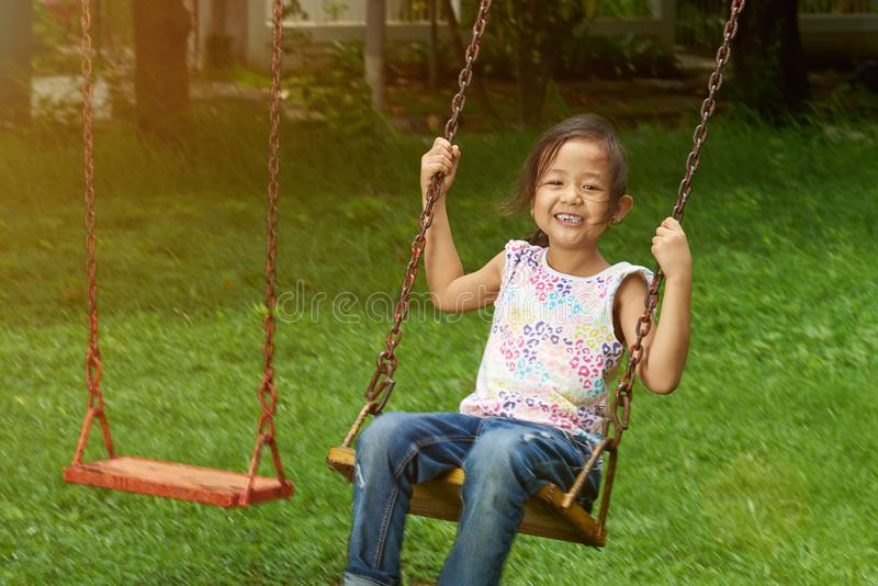 Liten asiatisk flickagunga parkerar in royaltyfria bilder