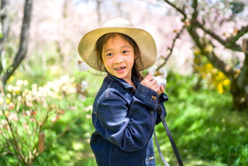 Liten asiatisk flickainnehavkamera som tar fotoet på att resa tur under semester arkivbilder
