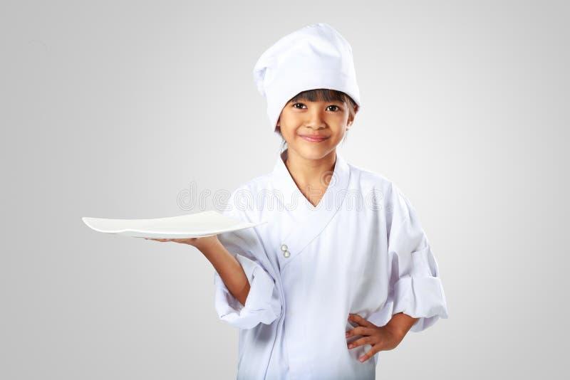 Liten asiatisk flickakock som visar den tomma vita plattan royaltyfria foton