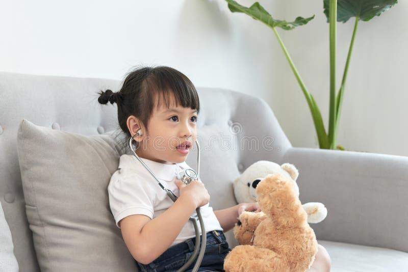 Liten asiatisk flickalek med behandla som ett barn - dockaleksaken Den lilla asiatiska flickah?llstetoskopet i hand och kontrolle arkivfoto