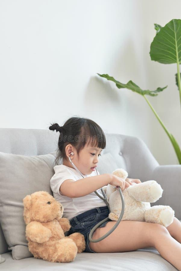 Liten asiatisk flickalek med behandla som ett barn - dockaleksaken Den lilla asiatiska flickah?llstetoskopet i hand och kontrolle arkivbild