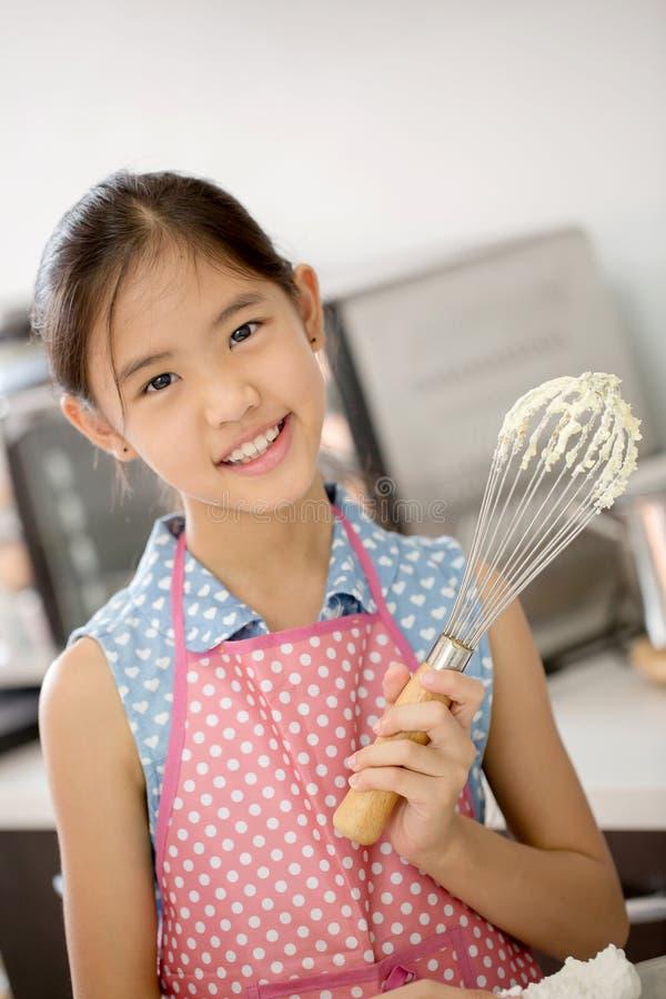 Liten asiatisk gullig kock som lagar mat ett bageri i kök royaltyfri foto