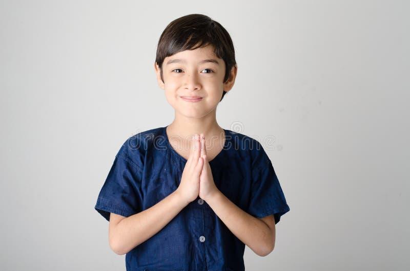 Liten asiatisk pojke som ber i thailändsk dräkt arkivfoto