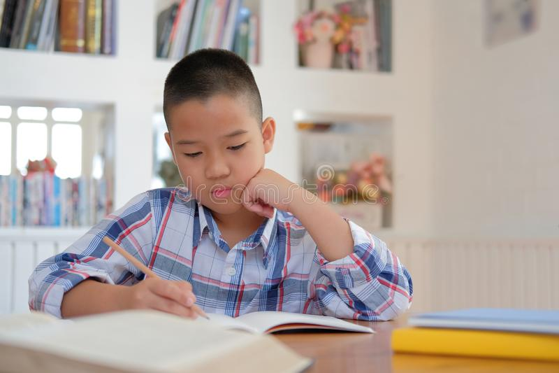 liten asiatisk ungepojkeskolpojke som skriver teckningen på anteckningsboken Chil royaltyfria bilder