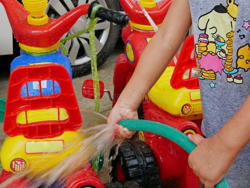Liten babys händer som spelar vatten och lär att tvätta plast- stora cyklar royaltyfria bilder