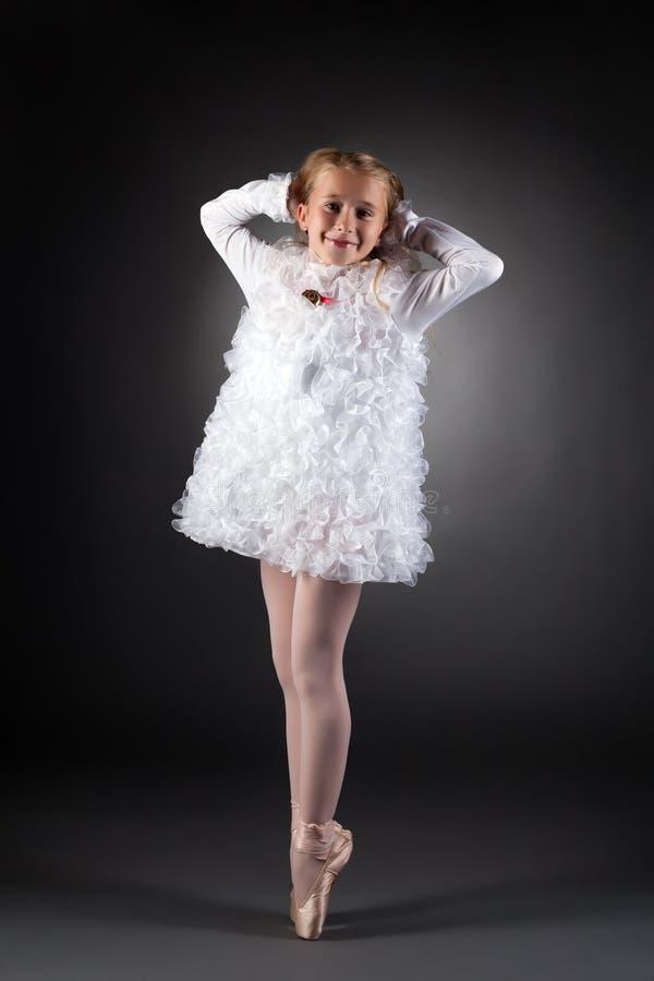 Liten balettdansör som poserar i den vita klänningen arkivbilder