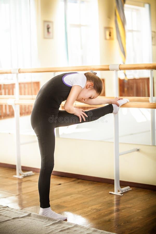 Liten balettdansör som sträcker i dansgrupp arkivfoto
