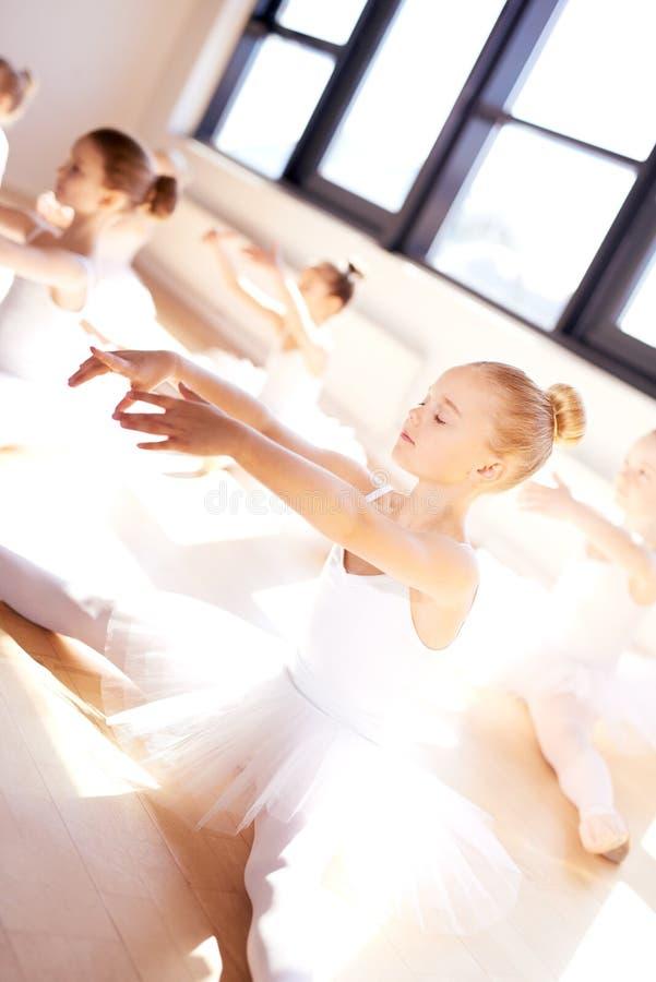 Liten balettflicka i utbildning med hennes klasskompisar fotografering för bildbyråer