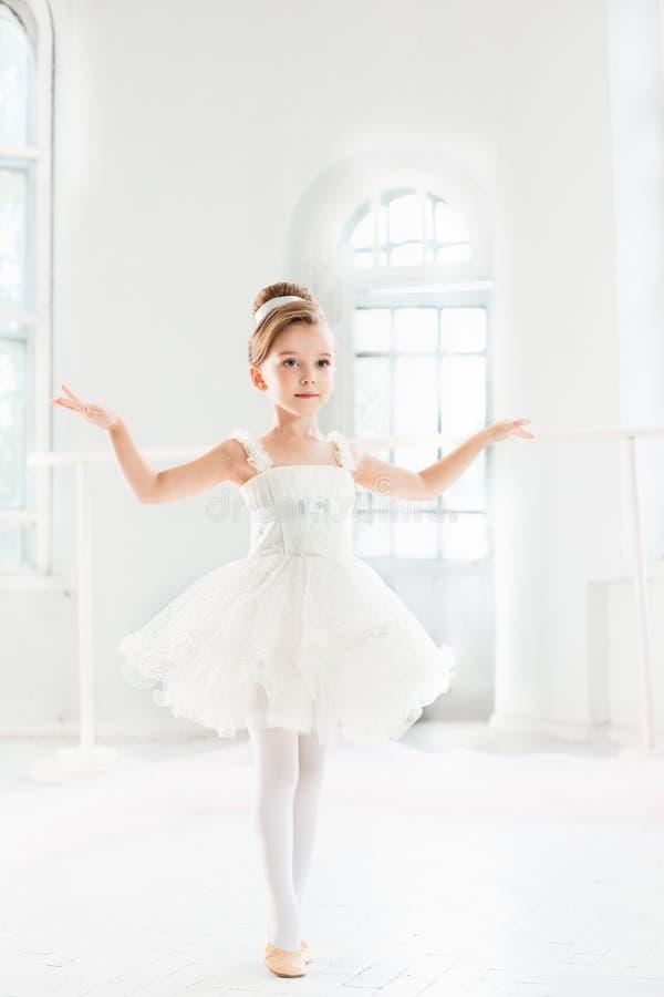 Liten ballerinaflicka i en ballerinakjol Förtjusande barn som dansar klassisk balett i en vit studio royaltyfri fotografi
