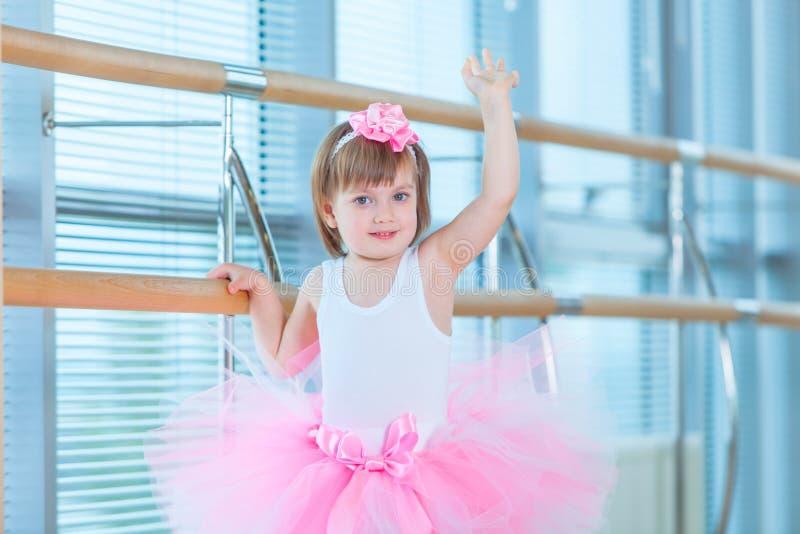 Liten ballerinaflicka i en rosa ballerinakjol Förtjusande barn som dansar klassisk balett i en vit studio Barndans ungar arkivbild