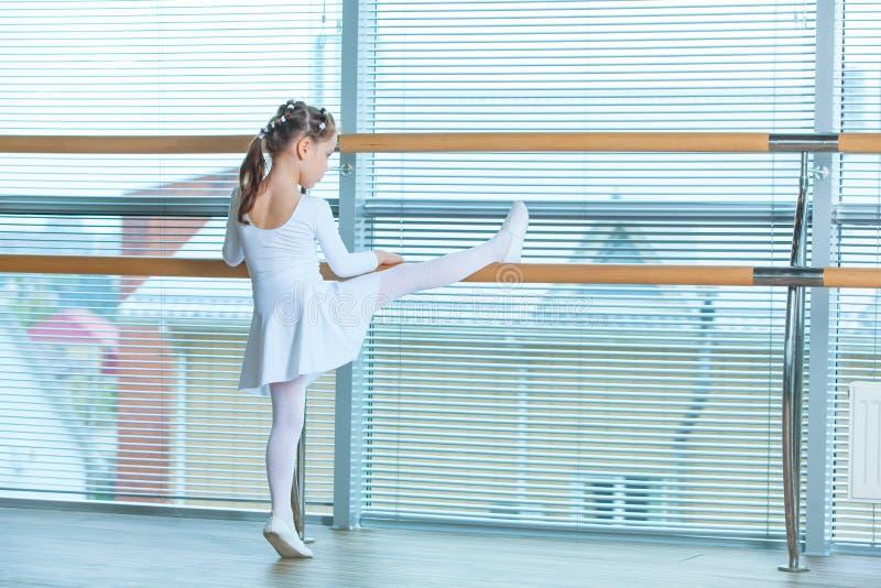 Liten ballerinaflicka i en rosa ballerinakjol Förtjusande barn som dansar klassisk balett i en vit studio Barndans ungar royaltyfri foto