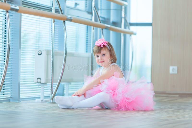 Liten ballerinaflicka i en rosa ballerinakjol Förtjusande barn som dansar klassisk balett i en vit studio Barndans ungar arkivfoto