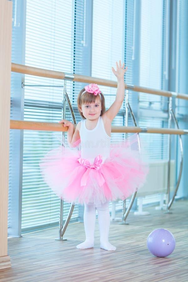 Liten ballerinaflicka i en rosa ballerinakjol Förtjusande barn som dansar klassisk balett i en vit studio Barndans ungar fotografering för bildbyråer