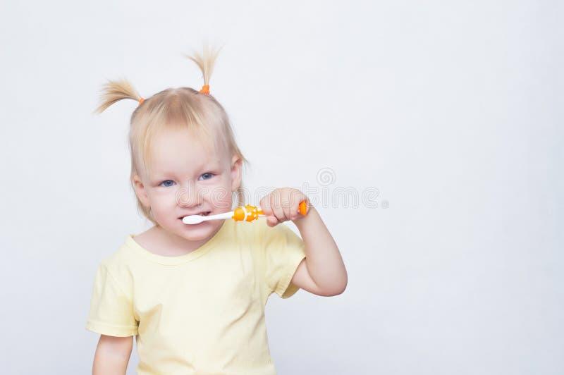 Liten blåögd flickablondin med råttsvansar på hennes huvud som borstar tänder med en tandborste och ser kameran fotografering för bildbyråer