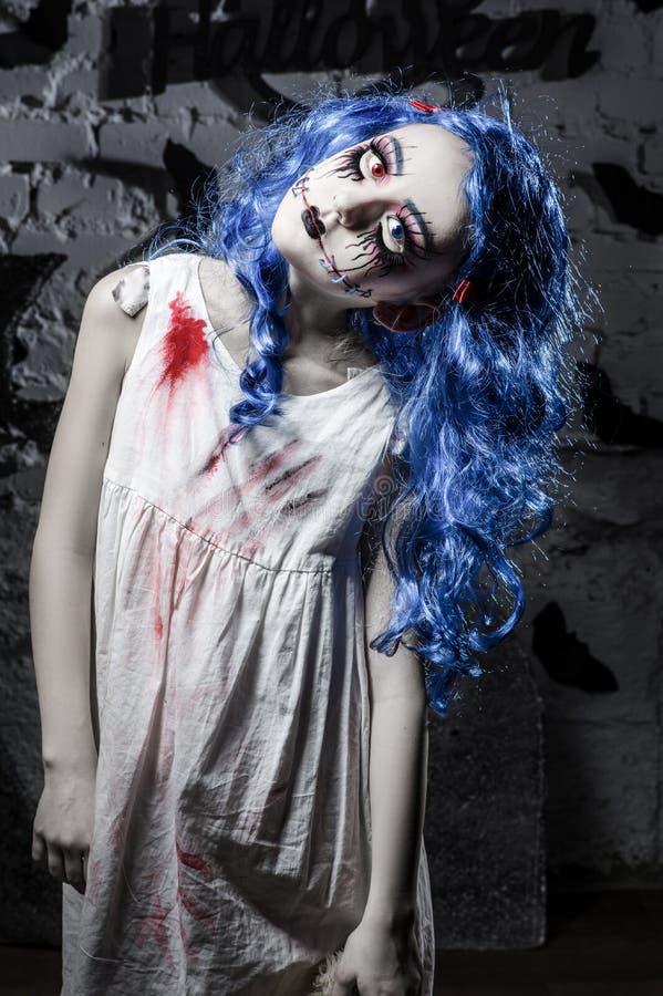 Liten blå hårflicka i blodig klänning med läskig halloween makeup arkivfoto