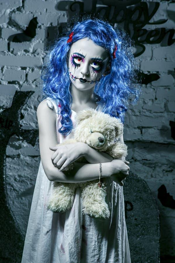 Liten blå hårflicka i blodig klänning med läskig halloween makeup arkivfoton