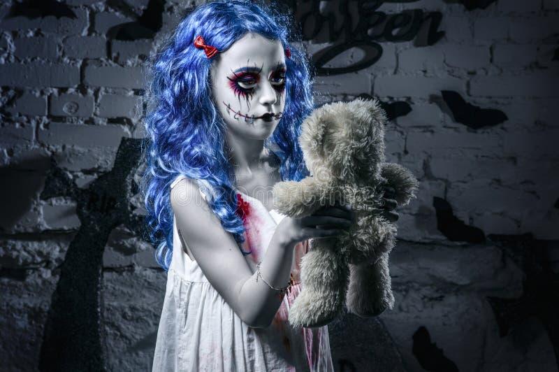 Liten blå hårflicka i blodig klänning med läskig halloween makeup med nallebjörnen royaltyfri bild