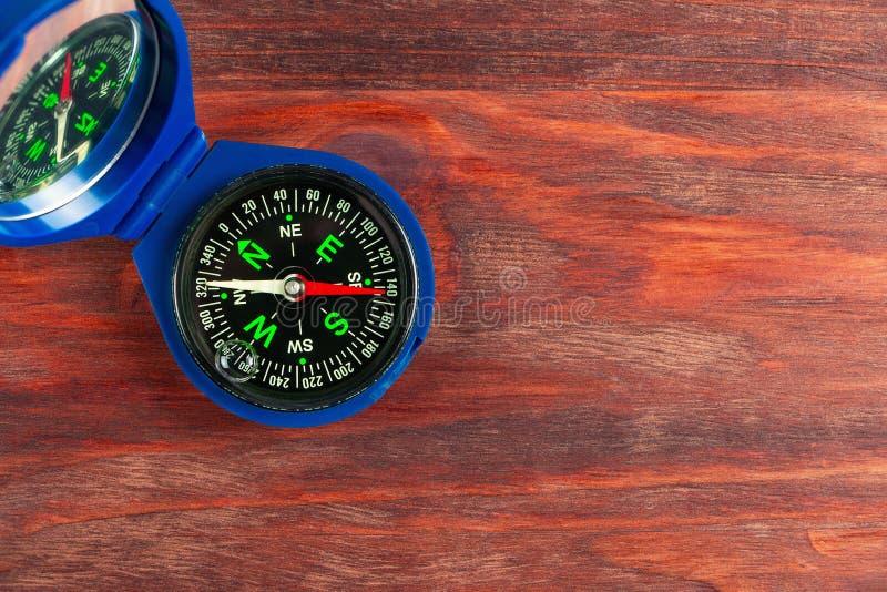 Liten blå kompass på träyttersida royaltyfria foton