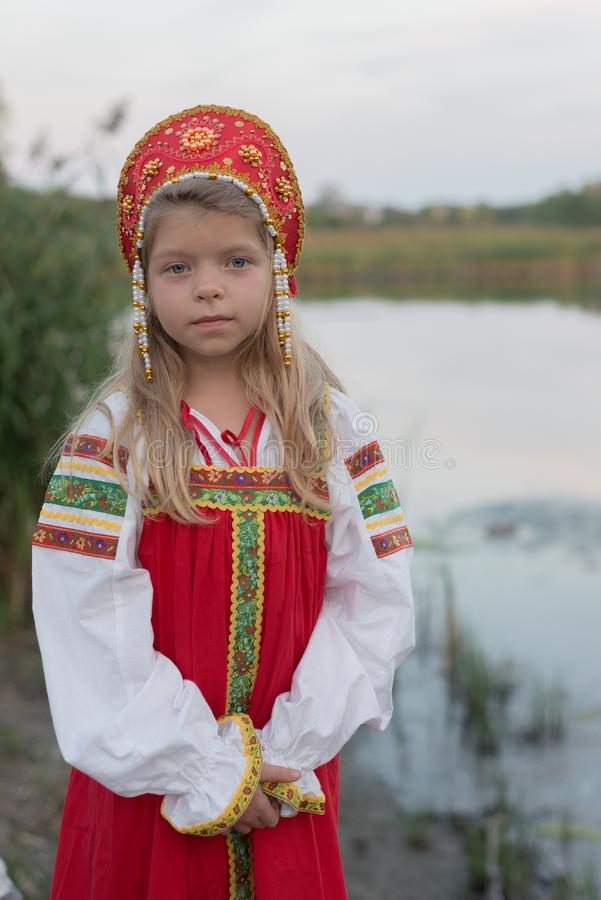 Liten blond Caucasian flicka i rysk nationell dräkt på naturlig landskapbakgrund för suddighet arkivfoton