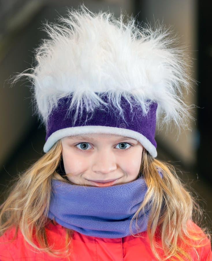 Liten blond flicka i rolig hatt för konstgjord päls royaltyfri fotografi