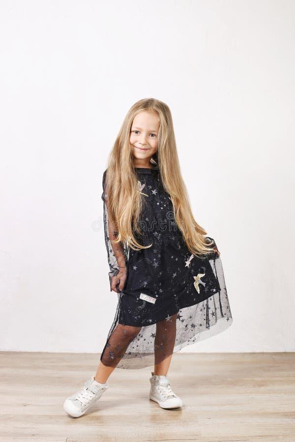 Liten blond flicka med långt guld- hår som bär den svarta klänningen med stjärnor & planeter, dans, smling & har gyckel, vit vägg arkivbilder