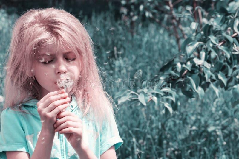 Liten blond flicka som blåser maskrosen arkivfoto