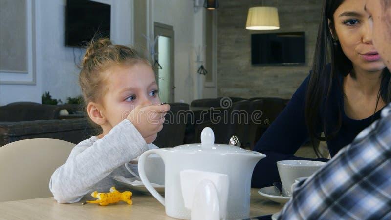 Liten blond flicka som dricker tesammanträde i kafé med hennes älskvärda föräldrar royaltyfri fotografi