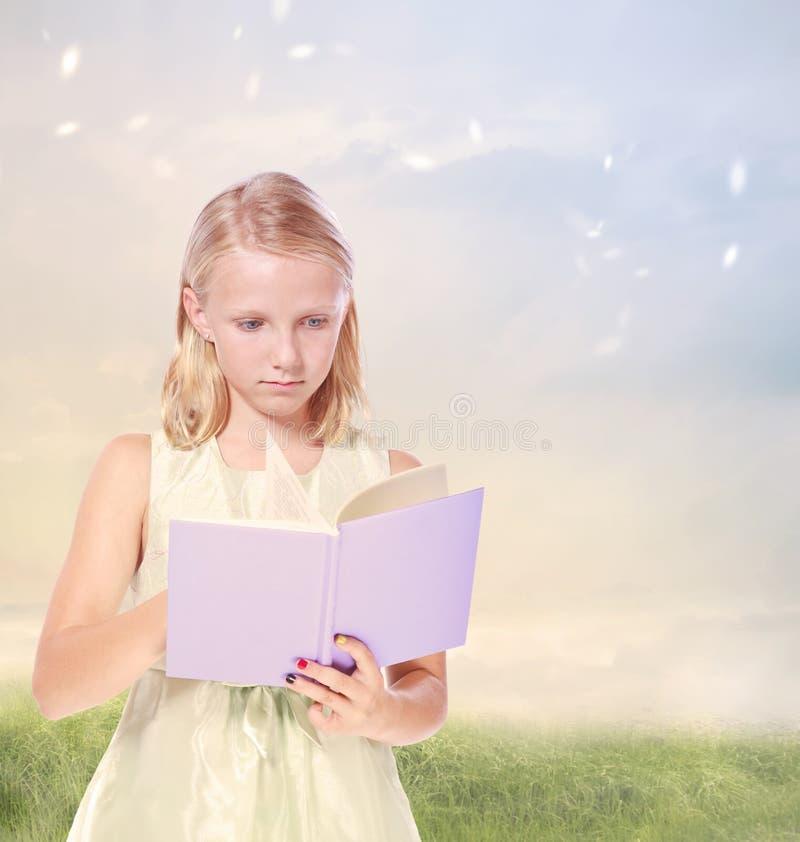 Liten blond flicka som läser en bok royaltyfria bilder