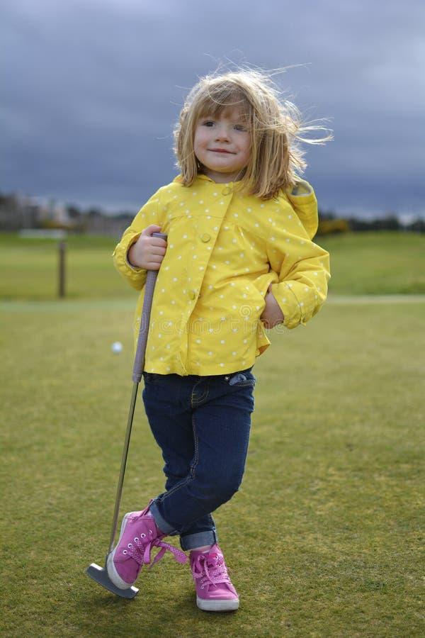 Liten blond flicka som spelar en lek av golf royaltyfri foto