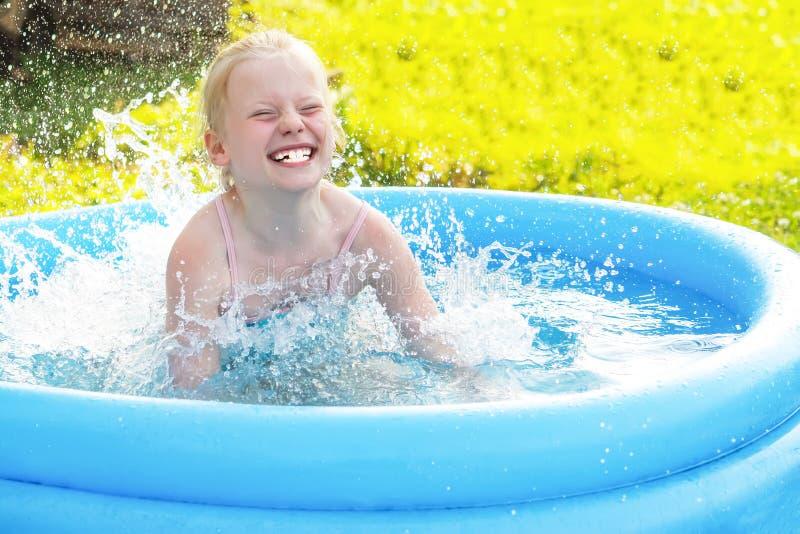 Liten blond flicka som spelar i utomhus- simbassäng på varm sommardag arkivbilder