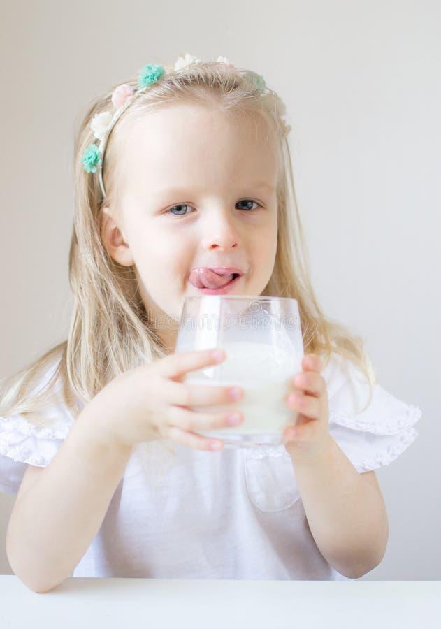 Liten blond flickadrink som ett exponeringsglas av mjölkar med olika sinnesrörelser royaltyfri fotografi