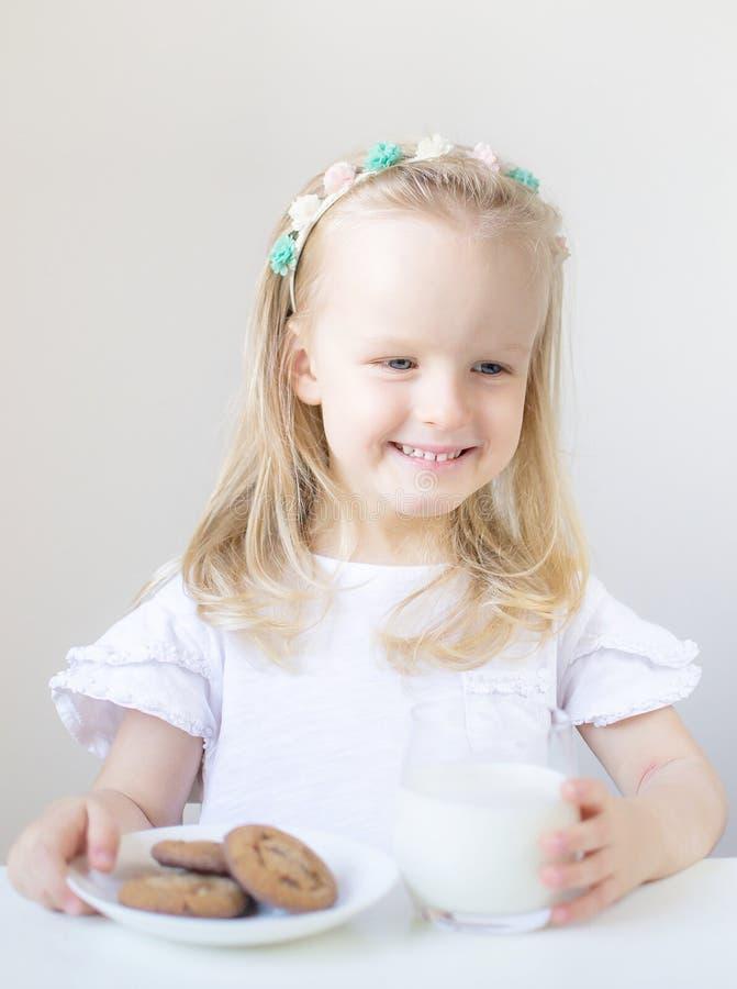 Liten blond flickadrink som ett exponeringsglas av mjölkar med olika sinnesrörelser royaltyfria foton