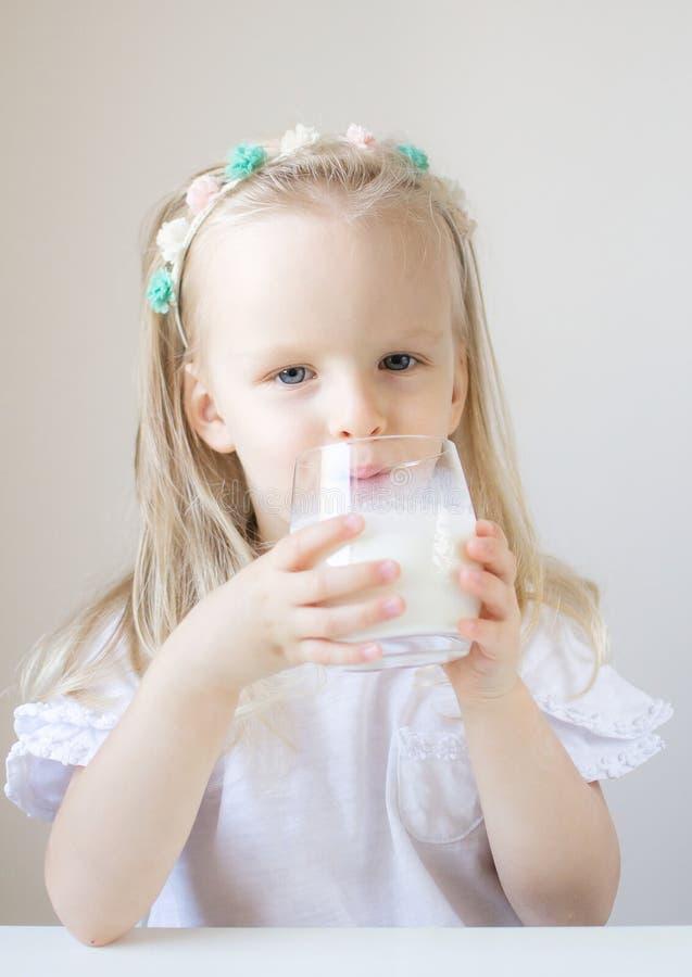 Liten blond flickadrink som ett exponeringsglas av mjölkar med olika sinnesrörelser royaltyfria bilder