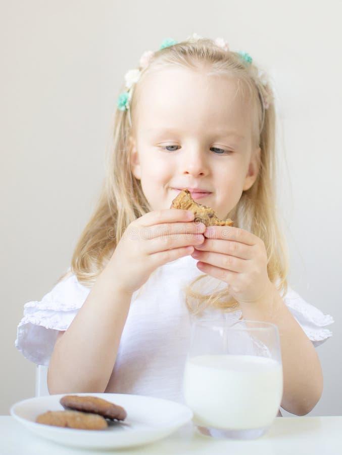 Liten blond flickadrink som ett exponeringsglas av mjölkar med olika sinnesrörelser arkivfoto