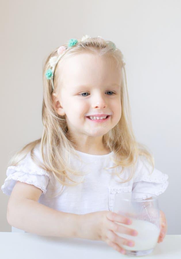 Liten blond flickadrink som ett exponeringsglas av mjölkar med olika sinnesrörelser royaltyfri bild