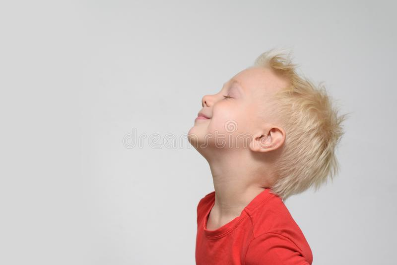 Liten blond pojke i en r?d T-tr?ja med st?ngda ?gon fr?n n?je Utrymme f?r text Vit bakgrund arkivfoton
