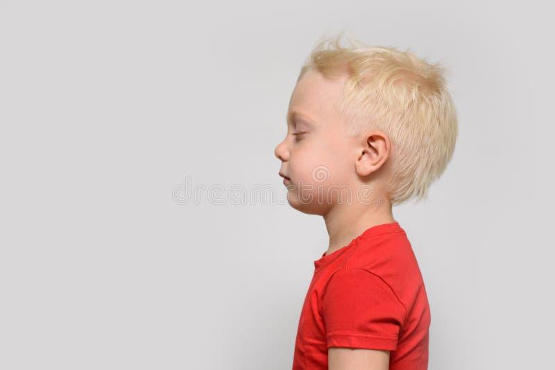 Liten blond pojke i r?d t-skjorta med st?ngda ?gon Utrymme f?r text Vit bakgrund arkivbilder