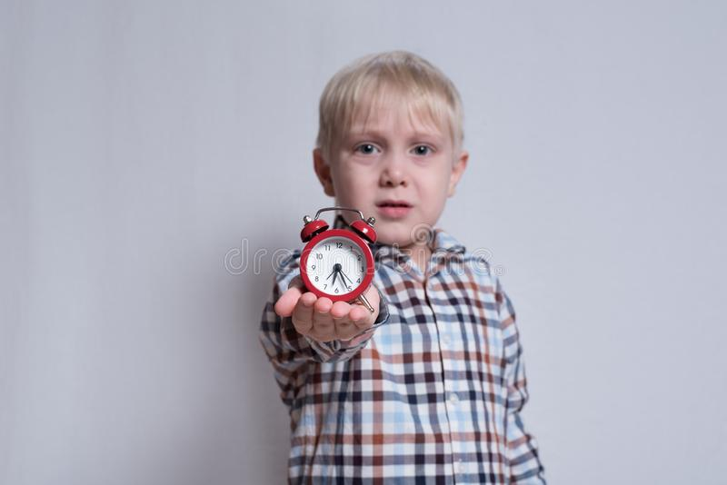 Liten blond pojke med en r?d ringklocka i hans h?nder Ta tid p? som den kaffekoppen, tidningen och penna Ljus bakgrund royaltyfria bilder