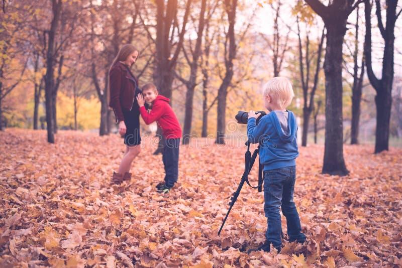 Liten blond pojke med en stor SLR kamera på en tripod Fotografier en gravid moder och son Familjfotoperiod arkivfoton
