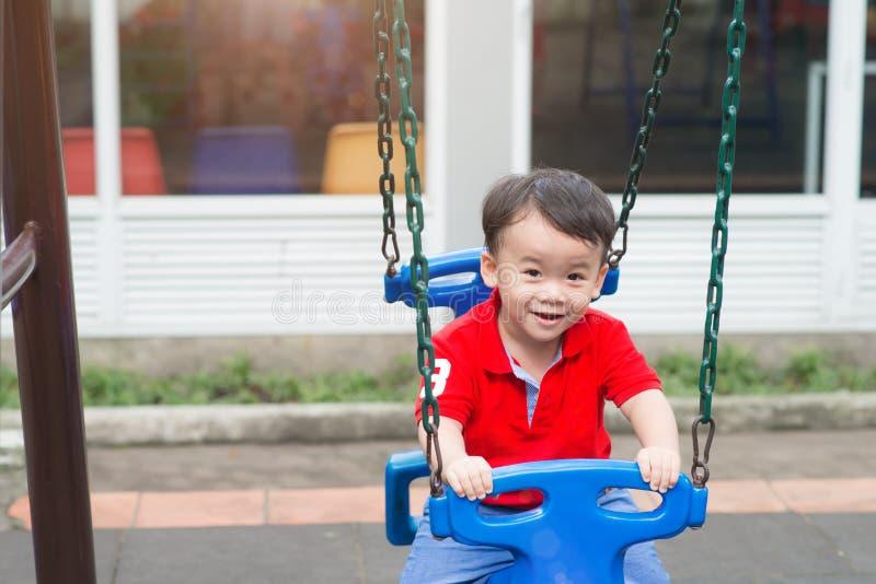 Liten blond pojke som har gyckel på lekplatsen royaltyfri fotografi