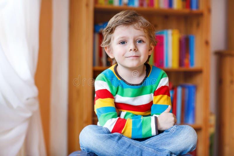 Liten blond ungepojke som framme sitter av bokhyllan arkivbilder
