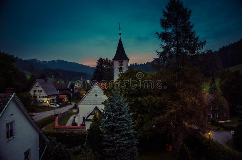 Liten by Bolsternang med kyrkan, södra Tyskland, på solnedgången fotografering för bildbyråer