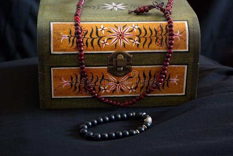 Liten bröstkorg med målade prydnader för gammal skola och den prydde med pärlor halsbandet fotografering för bildbyråer